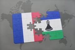 déconcertez avec le drapeau national des Frances et du Lesotho sur un fond de carte du monde Images stock