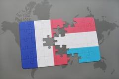 déconcertez avec le drapeau national des Frances et du Luxembourg sur un fond de carte du monde Photos stock