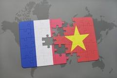 déconcertez avec le drapeau national des Frances et du Vietnam sur un fond de carte du monde Images libres de droits