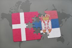 déconcertez avec le drapeau national du Danemark et de la Serbie sur un fond de carte du monde Photographie stock