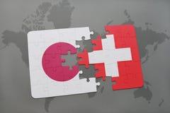 déconcertez avec le drapeau national du Japon et de la Suisse sur un fond de carte du monde Photographie stock libre de droits