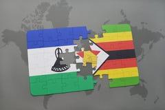 déconcertez avec le drapeau national du Lesotho et du Zimbabwe sur une carte du monde Photos stock
