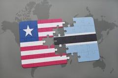 déconcertez avec le drapeau national du Libéria et du Botswana sur une carte du monde Photos libres de droits