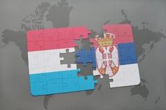 déconcertez avec le drapeau national du Luxembourg et de la Serbie sur un fond de carte du monde Image stock