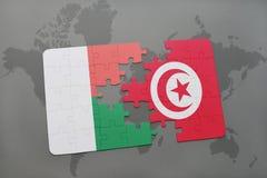 déconcertez avec le drapeau national du Madagascar et de la Tunisie sur une carte du monde Image stock