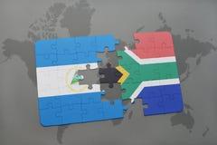 déconcertez avec le drapeau national du Nicaragua et de l'Afrique du Sud sur une carte du monde Photographie stock