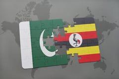déconcertez avec le drapeau national du Pakistan et de l'Ouganda sur un fond de carte du monde Image libre de droits