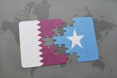 déconcertez avec le drapeau national du Qatar et de la Somalie sur un fond de carte du monde Images libres de droits