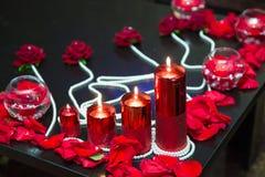 Décoré des bougies rouges et des pétales rouges Des perles sont enveloppées autour Image libre de droits