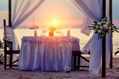 Décoré pour une table de dîner romantique sur la plage sablonneuse Contre le contexte du coucher du soleil, des yachts et des mon photos libres de droits