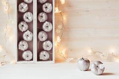 Décor à la maison mou de Noël des pommes argentées et des lumières brûlant dans des boîtes sur un fond blanc en bois Images libres de droits