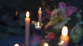 Décor avec le vase en verre avec des fleurs dans lui, allumé bougies autour de lui clips vidéos