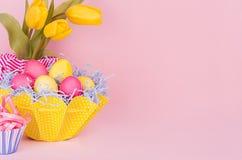 Décor de maison de ressort de Pâques des tulipes jaunes, oeufs peints, petit gâteau sur le fond rose mou en pastel images libres de droits
