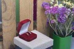 Décor de mariage Anneaux de mariage dans une boîte, mensonge sur la surface de tissu Un bouquet des fleurs sèches tout près Photo libre de droits
