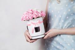 Décor de mariage : la fille dans une robe de globe tient une boîte ronde avec un bouquet des roses roses Image libre de droits