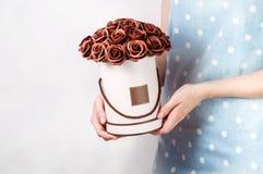 Décor de mariage : la fille dans une robe de globe tient une boîte ronde avec un bouquet des roses brunes Images libres de droits