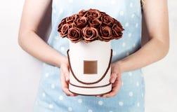 Décor de mariage : la fille dans une robe de globe tient une boîte ronde avec un bouquet des roses brunes Photos libres de droits