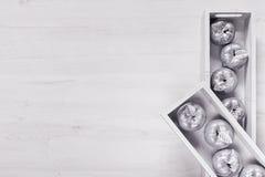 Décor de Noël des pommes argentées dans des boîtes sur le fond blanc en bois Images stock