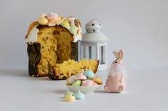 Décor de Pâques avec les meringues colorées, le gâteau de Pâques et un lapin rose en pastel de couleur photographie stock