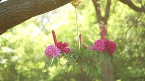 Décor de table de mariage avec les bougies accrochantes décorées des fleurs sensibles cérémonie de mariage extérieure banque de vidéos