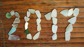 Décor en verre de bord de la mer sur le fond en bois Mosaïque en verre de mer de la nouvelle année 2017 Image stock