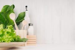 Décor moderne blanc de cuisine avec le plat en bois naturel beige, ustensiles, salade verte fraîche sur le fond en bois photo libre de droits