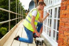 Décorateur sur l'échafaudage peignant la Chambre extérieure Windows Photos stock