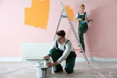 D?corateurs professionnels peignant le mur Service des r?parations ? la maison photo stock