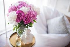 Décoration à la maison, pivoines roses fraîches sur la table basse dans le roo blanc Image stock