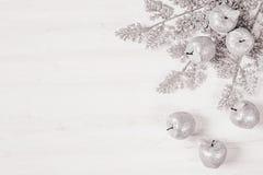 Décoration argentée de brins et de pommes de Noël sur le fond blanc en bois Photo stock