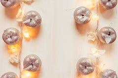 Décoration argentée et lumières de pommes de Noël brûlant sur un fond en bois beige Photos libres de droits