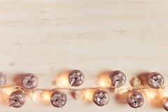 Décoration argentée et lumières de pommes de Noël brûlant sur un fond en bois beige Photos stock