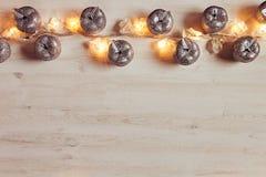 Décoration argentée et lumières de pommes de Noël brûlant sur un fond en bois beige Photographie stock