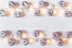 Décoration argentée et lumières de pommes de Noël brûlant sur un fond en bois blanc Photographie stock libre de droits