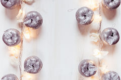Décoration argentée et lumières de pommes de Noël brûlant sur un fond en bois blanc Photos stock