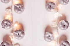 Décoration argentée et lumières de pommes de Noël brûlant sur un fond en bois blanc Photo libre de droits