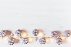 Décoration argentée et lumières de pommes de Noël brûlant sur un fond en bois blanc Image libre de droits