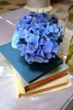 Décoration bleue de fleur placée sur vieux livres sur un autel de mariage photo stock
