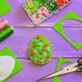 Décoration créative d'oeuf de pâques avec les fleurs en plastique Oeuf de feutre avec le modèle floral, ciseaux, calibre de papie Photographie stock