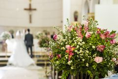 Décoration d'église catholique pour des cérémonies de mariage - jeunes mariés sur le fond nu - image libre de droits