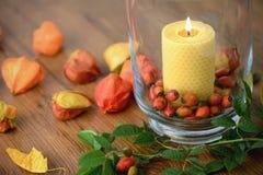 Décoration d'automne avec les cynorrhodons et la bougie brûlante en verre Images stock