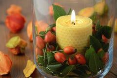 Décoration d'automne avec les cynorrhodons et la bougie brûlante en verre Images libres de droits