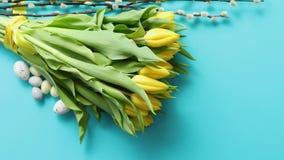Décoration de contept de vacances avec des oeufs de pâques et des tulipes jaunes au-dessus de bleu banque de vidéos