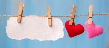 Décoration de forme de coeur de papier blanc et de couples accrochant sur la ligne avec l'espace de copie pour le texte sur le fo images libres de droits