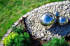 Décoration de jardin avec les sphères argentées de miroir Photographie stock