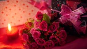 Décoration de longueur du bouquet de fleur, du cadeau et de la bougie rouge brûlant pour Valentine banque de vidéos