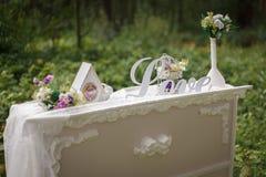 Décoration de mariage amour d'inscription, horloge, bouquet sur la table Photos stock