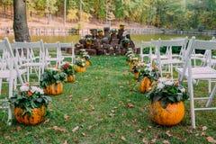 Décoration de mariage avec des potirons et des fleurs d'automne Cérémonie extérieure en parc Chaises blanches pour des invités Images stock