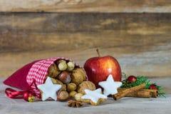 Décoration de Noël avec des écrous, des biscuits d'étoile, la pomme rouge et des épices aromatiques photo stock