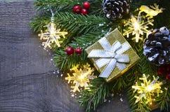 Décoration de Noël avec l'arbre de sapin, le boîte-cadeau d'or, les lumières de guirlande et les cônes de pin sur le vieux fond e Images libres de droits